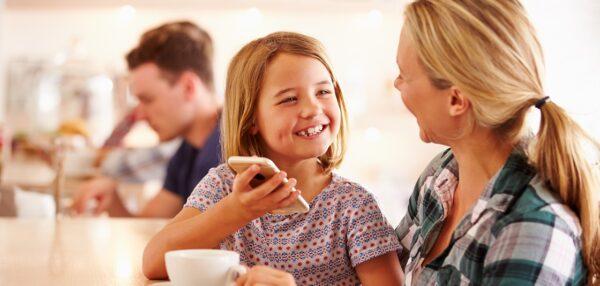 laps näitab emale kohvikus mobiili