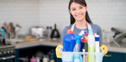 Portrait of a housekeeper holding cleaning products while working at home and looking at the camera smiling