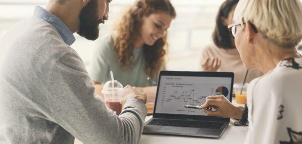 inimesed laua ümber arvutist jooniseid vaatamas